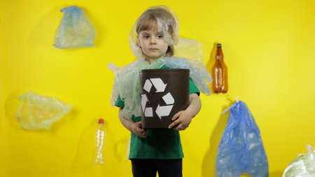 Sad girl activist in t-shirt with recycle logo in plastic packages on her neck and head. Background with cellophane bags, bottles. Reduce trash plastic pollution. Think green. Save ecology environment