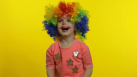 Child girl clown in colorful wig making silly faces. Happy five years old little caucasian kid having fun, smiling, dancing, looking at camera. Expressions. Halloween. Yellow background. Chroma Key