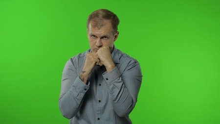 Funny handsome guy trying to fight at camera, boxing with expression. Portrait of young caucasian man 30s posing in shirt isolated on chroma key background in studio. People emotions concept