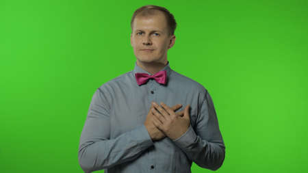 Handsome open-hearted lovely man giving from heart, gesturing Take it for free, looking kindly, sharing love care, generosity concept. Portrait of guy posing isolated on chroma key background Banco de Imagens