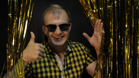 Portrait of young stylish caucasian man posing in shirt and sunglasses isolated on black background. Gold shining foil strips. People emotions. Party, music, lifestyle, radio and disco concept