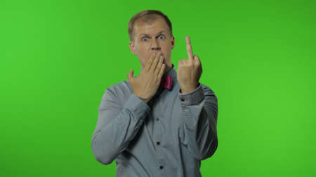 Funny man showing middle finger, demonstrating protest hate, impolite rude gesture of disrespect, aggressively rejecting communication. Portrait of guy on chroma key background. People emotions