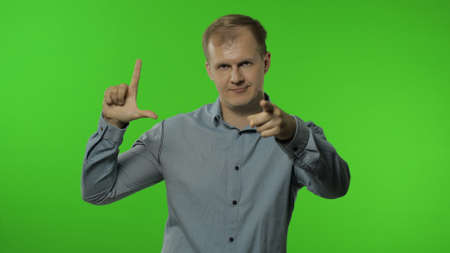 Guy showing loser gesture, pointing finger to camera, sarcastic smile, blaming for failure, lost job. Portrait of man 30s posing in shirt isolated on chroma key background in studio. People emotions Imagens