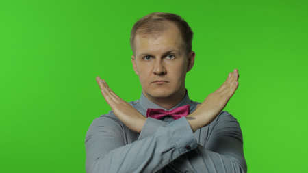 Displeased serious man crossed his arms in X sign and saying no, warning of finish, prohibited access, declining communication, body language. Portrait of guy on chroma key background