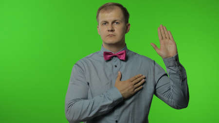 I swear. Worried honest man raising his hand up, touching chest and making sincere promise, taking oath with responsible expression. Portrait of guy posing on chroma key background. People emotions Stockfoto