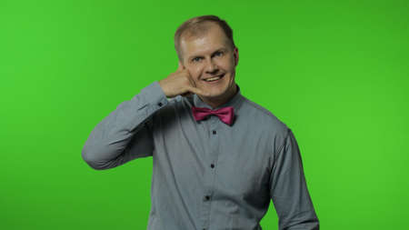 Hello, call me. Happy man standing with telephone hand gesture near head and pretending to communicate by phone, pointing finger to camera. Portrait of guy on chroma key background. People emotions
