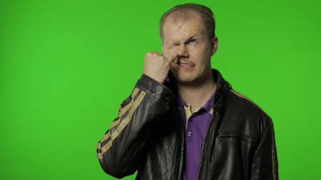 Funny stupid rocker man in jacket picking nose with silly brainless humorous expression, removing boogers, uncultured habit, bad manners. Portrait of guy biker on chroma key background Stock Photo