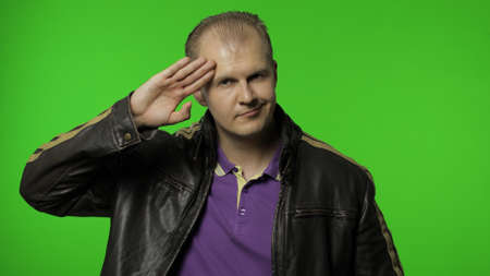 Positive rocker man in leather jacket saluting with hand, saying yes sir and looking at camera with humorous mockery expression, pretending to listen order. Guy biker on chroma key background