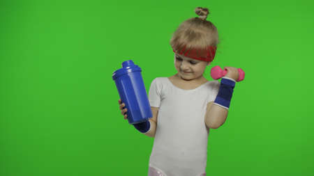 Young caucasian girl in white sportswear making fitness exercises with dumbbells and drinking water for refreshment. Workout for kids. Little athletic child in sports suit on chroma key background