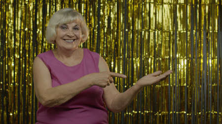 Amazed senior old woman in pink blouse pointing empty place on her palm, copy space advertising area on hand, expressing excited surprised emotions. Elderly grandma on golden background