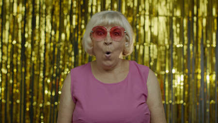 Portrait of excited wondered senior old blond woman looking around, opening her mouth in amazement, looking surprised shocked. Elderly stylish lady grandma on golden background in studio Stock fotó