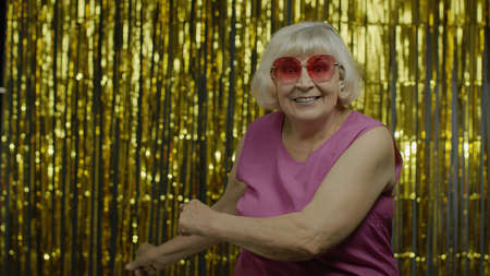 Amazed senior old woman in pink blouse pointing empty place behind her, copy space advertising area on hand, expressing excited surprised emotions. Elderly grandma on golden background