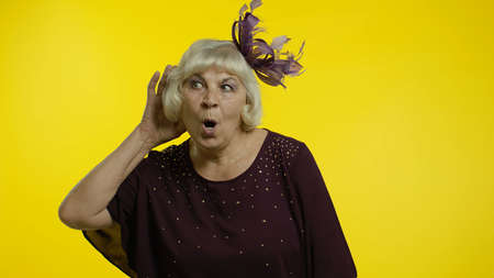 Portrait of senior old woman overhearing private conversation, trying to find out personal secrets, spying. Elderly stylish lady grandma on yellow background in studio
