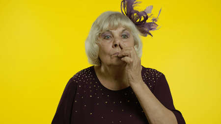 Funny stupid senior old woman picking nose with silly brainless humorous expression, removing boogers, uncultured habit, bad manners. Elderly stylish lady grandma on yellow background