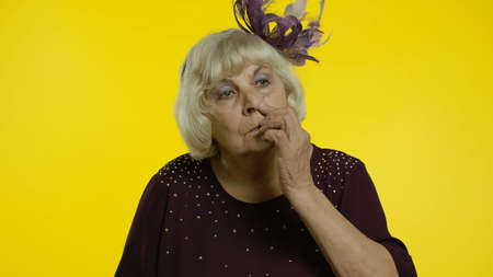 Funny stupid senior old woman picking nose with silly brainless humorous expression, removing boogers, uncultured habit, bad manners. Elderly stylish lady grandma on yellow background Foto de archivo