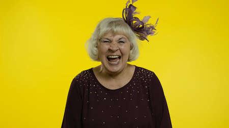 Happy joyful senior old woman laughing out loud after hearing ridiculous anecdote, funny joke, feeling carefree amused, positive lifestyle. Elderly stylish grandma on yellow background