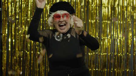 Happy joyful senior old woman shouting, raising fists in gesture I did it, celebrating success, winning lottery and goal achievement concept. Elderly grandma on golden background Stock fotó - 155430117