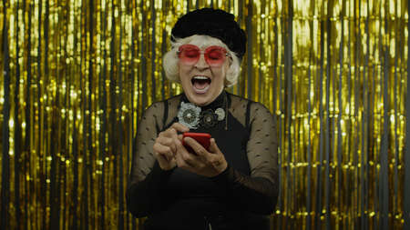 Shocked happy senior old woman with mobile phone. Shouting, celebrating success, winning lottery and goal achievement concept. Elderly stylish grandma