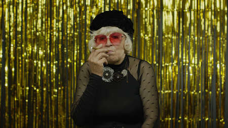 Elderly style granny caucasian mature woman in sunglasses posing, smoke electronic cigarette on golden background. Trendy old grandmother in fashion black clothes. Senior people