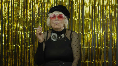 Elderly style granny caucasian mature woman in sunglasses posing, smoke cigarette on golden background. Trendy old grandmother in retirement age in fashion black clothes. Senior people