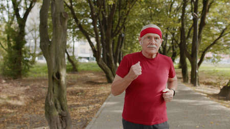 Senior old man running in city park and using earphones and listening music, enjoying healthy active lifestyle. Elderly male runner working out cardio morning exercise outdoor Stock fotó