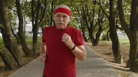 Male senior person running along the road in city park. Mature runner man training outside, listening music in portable modern earphones, enjoying nature. Healthy lifestyle of old people