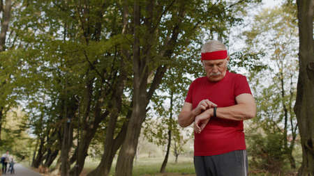 Senior sport runner man using smart watch, tapping touchscreen, tracking distance, checking pulse after fitness workout. Cardio outside in morning park. Active grandparent concept