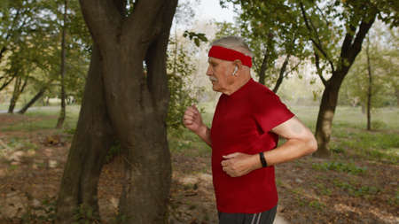 Side view of senior male person running along the road in park. Mature runner man training, listening music in portable modern earphones, enjoying nature. Healthy lifestyle of old people Stock fotó