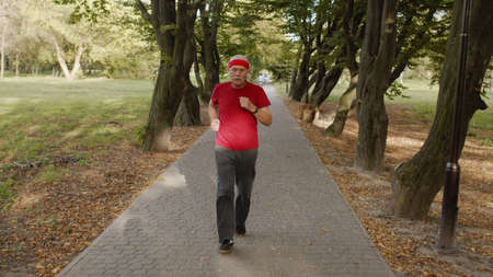 Senior old man running in city park and using bluetooth earphones and listening music, enjoying healthy active lifestyle. Elderly male runner working out cardio morning exercise outdoor