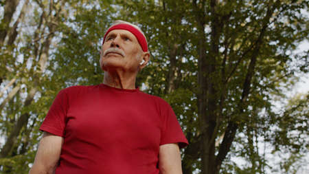 Senior old man runner in city park listening music, enjoying healthy active lifestyle. Elderly male working out cardio morning exercise outdoor