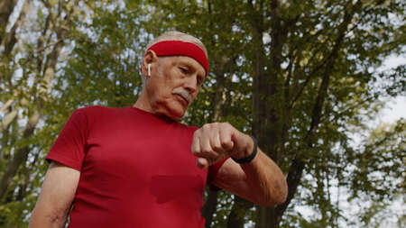 Senior sport runner man using smart watch, tracking distance, checking pulse after fitness workout. Cardio outside in morning park. Active grandparent concept Stock fotó