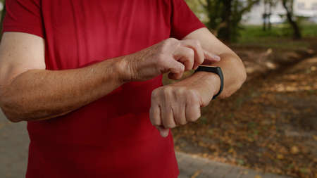 Senior old runner man starting tapping touchscreen on smart watch, tracking distance, checking pulse during fitness workout. Heart rate monitor before jogging. Healthy lifestyle concept