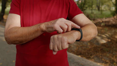 Adult runner man starting tapping touchscreen on smart watch, tracking distance, checking pulse during fitness workout. Heart rate monitor before jogging. Healthy lifestyle concept