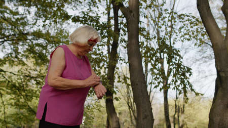 Senior sport runner woman using smart watch, tapping touchscreen, tracking result after fitness workout. Cardio outside in city park at summer morning. Old grandmother enjoying sport