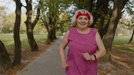 Senior old woman running in city park and using smart watch, enjoying healthy active lifestyle. Elderly female runner working out cardio morning exercise outdoor. Active sport people