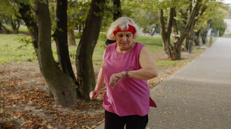 Female senior person running along the road in city park. Mature runner woman training outside, enjoying nature. Workout cardio at summer morning. Healthy lifestyle of old people Stock fotó