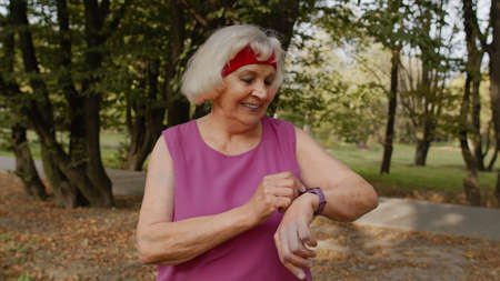 Senior sport runner woman using smart watch, tapping touchscreen, tracking distance, checking pulse after fitness workout. Cardio outside in morning park. Active grandparent concept