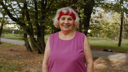 Senior old runner woman in city park enjoying healthy active lifestyle. Elderly female working out cardio morning exercise outdoor. Active sport people