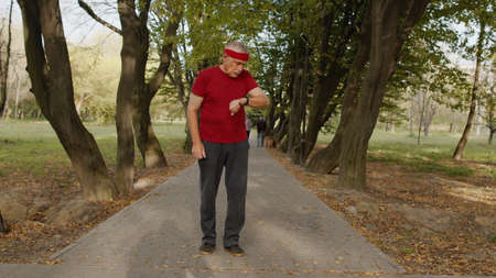 Senior sport runner man using smart watch, tapping touchscreen, tracking result after fitness workout. Cardio outside in city park at summer morning. Old grandfather enjoying sport Stock fotó