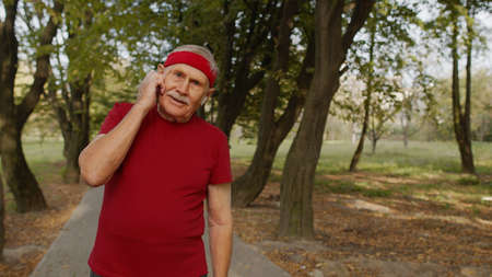 Senior old runner man in city park and using earphones and listening music, enjoying healthy active lifestyle. Elderly male working out cardio morning exercise outdoor Stock fotó