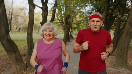 Active senior elderly runner couple 80 years old. Caucasian man and woman running in city park. Active family leisure. Cardio morning exercise workout. Healthy lifestyle leisure activity