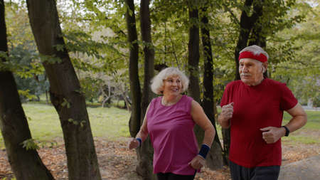 Happy sporty mature family couple jogging together. Senior husband and wife doing cardio workout exercises, running together in park. Leisure fitness activity for man and woman Stock fotó