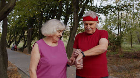 Happy sporty mature family couple together after running. Senior husband and wife using smart watch, tracking result of fitness cardio workout. Leisure fitness activity for man and woman Stock fotó