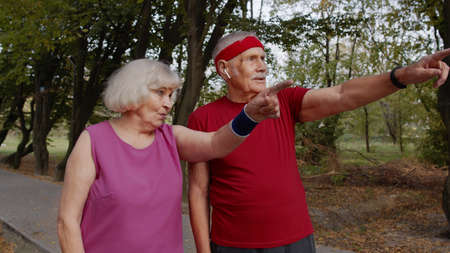 Excited sporty senior family couple making route for running. Husband and wife preparing for fitness cardio workout marathon. Leisure fitness activity for mature runner man and woman