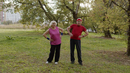 Active senior elderly couple 80 years old. Caucasian man and woman doing morning stretching physical workout exercises in park. Fitness grandparents family leisure. Healthy lifestyle Фото со стока