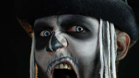 Close up footage of sinister man face with horrible Halloween skeleton makeup. Guy making faces, showing black teeth, trying to scare. Horror theme. Day of The Dead. Dark background