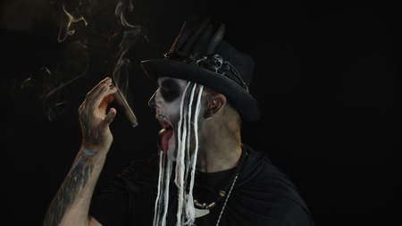 Portrait of scary guy in thematic carnival costume of Halloween skeleton against black background smoking cigar, making faces, showing tongue. Sinister man with professional skull makeup