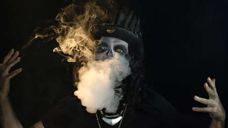 Frightening man in skeleton Halloween cosplay costume. Guy in creepy skull makeup exhaling cigarette smoke from his mouth and smiling. Smoking kills. Day of The Dead. Black background