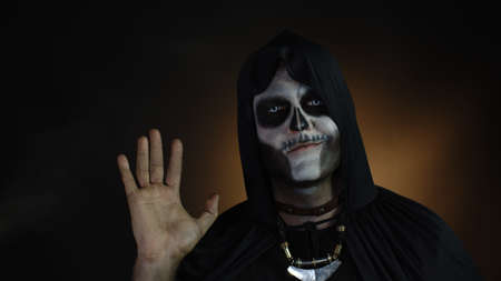 Frightening man in skeleton Halloween cosplay costume. Guy in creepy skull makeup waving hands looking at camera with smile, saying hi, hello, greeting. Day of The Dead. Black background