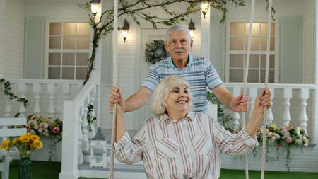 Senior Caucasian couple together in front yard at home. Man swinging and hugging woman. Happy mature family of grandfather and grandmother resting and enjoying communication